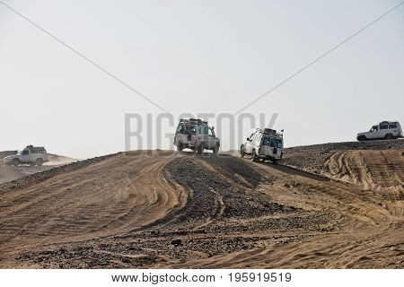 Vehicles driving in dusty desert on white sky background. Safari trip on 4x4 jeeps. Dune bashing. Offroad adventure. Extreme activity. Travel travelling. Summer vacation
