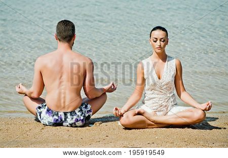 yoga couple relaxing doing meditation on beach man and woman people sitting in the lotus position at water