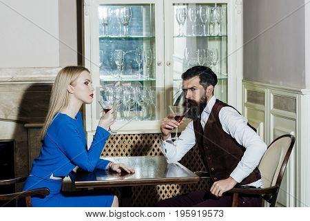 Boyfriend and girlfriend drinking red wine in restaurant. Woman or girl and man or hipster sitting with martini glasses at table. Couple in love. Date dating. Alcohol appetizer. Addictive convive