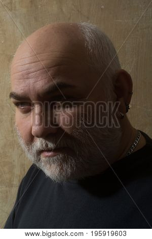 Grandfather with grey beard and moustache on old face with wrinkled skin and bald head. Senior man or male person in black sweater on beige wall. Hair loss. Time age and aging