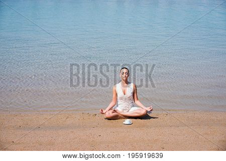 girl meditating sitting in yoga pose in sea ocean water on sand at sunny summer beach with coffee cup in morning idyllic vacation relax healthy lifestyle