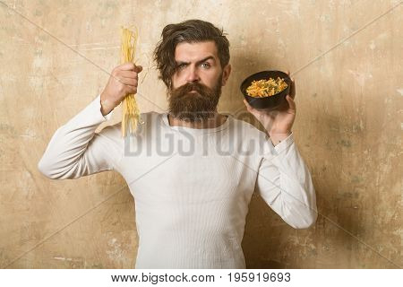 Hipster hold Italian macaroni. Man with pasta in hand. Cook or chef bearded man with bowl. Healthy food and dieting. Cooking raw spaghetti in restaurant.