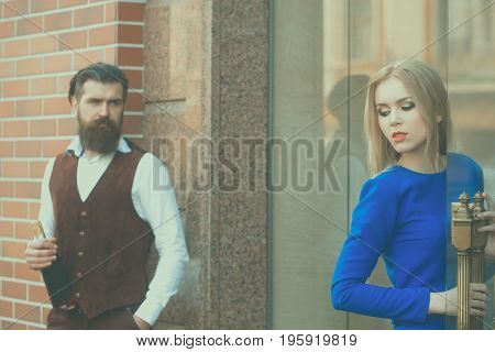 Hipster With Bottle Of Wine Looking At Woman Opening Door