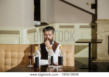 Hipster Sitting On Sofa With Martini Glass And Three Bottles