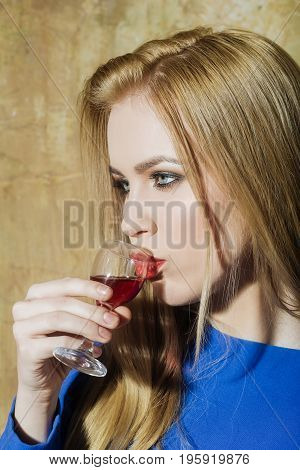 Woman drinking glass of red wine. Girl with blond long hair make up in blue dress on beige wall. Alcohol appetizer bad habits addictive and convive. Unhealthy lifestyle