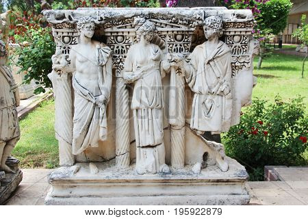 Antalya, Turkey - Jun 4 2017: Ancient stone Lycian sarcophagus with the sculptures of men and women in antique costumes - toga. in a Park on the street next to Antalya archaeological Museum. Turkey