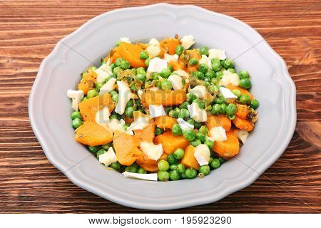 Warm salad with roasted pumpkin, peas and cheese brie. Low fat healthy eating concept.