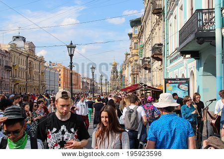 St. Petersburg, Russia - July 13 2017: Historic, picturesque street to Church on spilled blood full of pedestrians. Sunny summer day, a crowd of tourists. Lampposts, cafes, souvenir shops, blue sky.