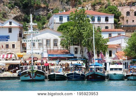 Antalya, Turkey- 29 May 2017: The view of the yachts and cruise boats in the old harbour of Kaleici and the sea and white buildings with red tile roofs against rocky cliffs. Travel background.