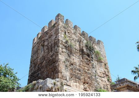The ancient crenellated tower at the ancient Hadrian's gate in Antalya, Turkey. On the background of blue sky and green trees.
