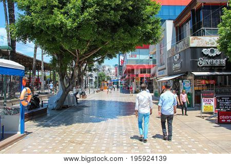 Antalya, Turkey - 1 Jun 2017: Modern town centre with a wide cobbled pedestrian streets with green trees, shops, cafes, people, tourists on a bright Sunny summer day background.