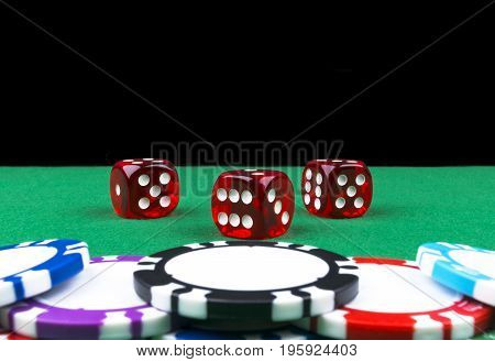 Stack of Poker chips on a green gaming poker table with poker dice at the casino . Playing a game with dice. Casino dice Concept for business risk chance good luck or gambling. chips and dice for poker