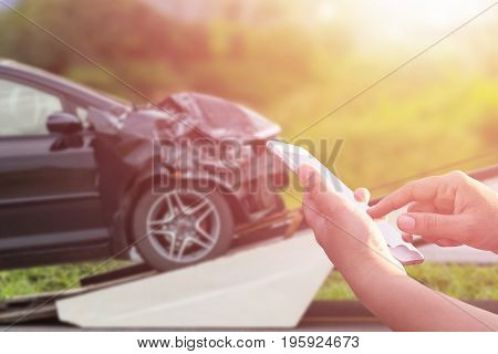 Hand Of Woman Using Smartphone And Blur Of Her Broken Car Parking On The Road. Contacting Car Techni