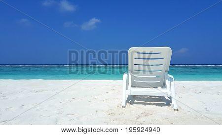 Maldives white sandy beach sunbed on sunny tropical paradise island with aqua blue sky sea ocean 4k