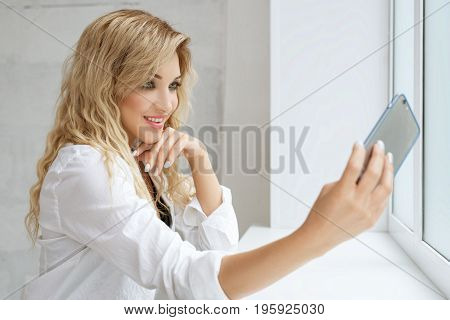 Beautiful blonde wearing white shirt making selfie by the window studio portrait