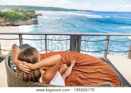 Young happy woman relaxing in lounge on roof veranda with beautiful tropical sea view. Positive girl look at ocean surf enjoy vacation. Healthy lifestyle people on family summer beach holiday.