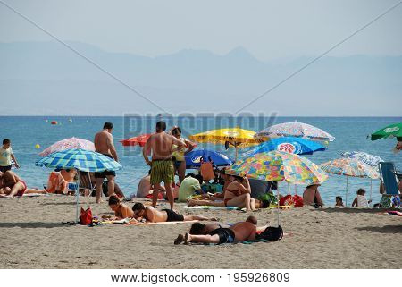 TORREMOLINOS, SPAIN - SEPTEMBER 3, 2008 - Holidaymakers relaxing on the beach Torremolinos Malaga Province Andalusia Spain Western Europe, September 3, 2008.