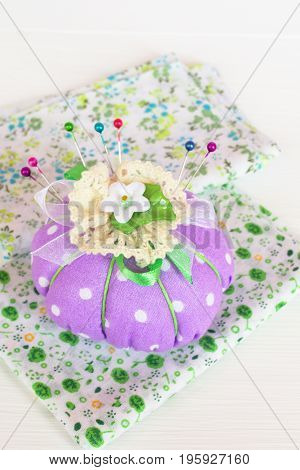 Pin cushion with pieces of cloth on white wooden background