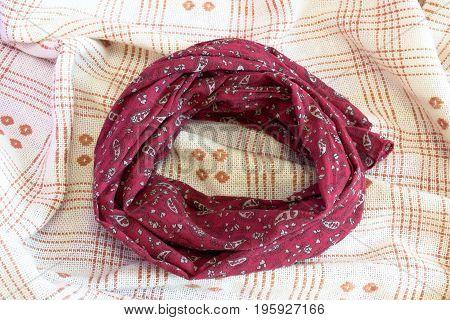 Burgundy scarf on beige background. Female accessory