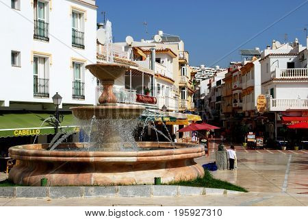 TORREMOLINOS, SPAIN - SEPTEMBER 3, 2008 - Fountain with pavement cafes and shops to the rear in La Carihuela district Torremolinos Malaga Province Andalusia Spain Western Europe, September 3, 2008.