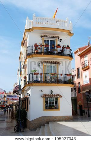 TORREMOLINOS, SPAIN - SEPTEMBER 3, 2008 - Typical Andalucian style corner building with balconies along a town centre shopping street Torremolinos Malaga Province Andalusia Spain Western Europe, September 3, 2008.