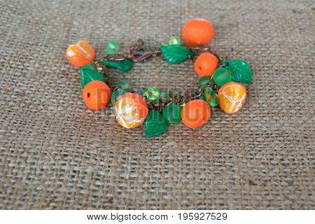Original bracelet with polymer clay mandarines and plastic beads and leaves