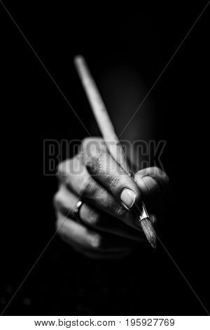 The Artist's Hands Hold A Brush