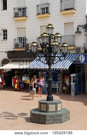 TORREMOLINOS, SPAIN - SEPTEMBER 3, 2008 - Ornate lamppost with shops to the rear along San Miguel street Torremolinos Malaga Province Andalusia Spain Western Europe, September 3, 2008.