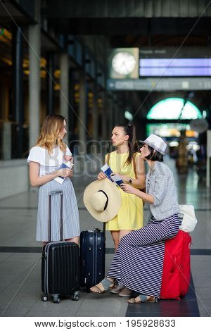 Young women in the waiting room at the railway station. In hands at girlfriends of the passport and tickets. Nearby suitcases. Travelers discuss something. Time of summer holidays.
