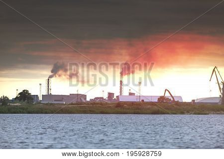 Air pollution by smoke coming out of two factory chimneys. Industrial zone in the city