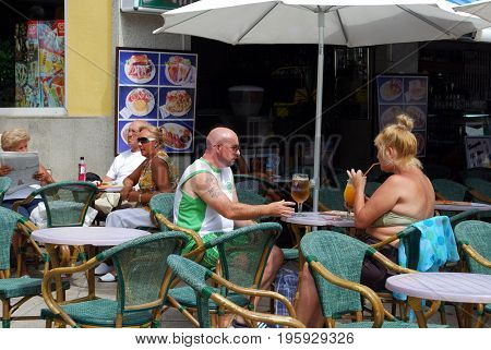 TORREMOLINOS, SPAIN - SEPTEMBER 3, 2008 - Tourists relaxing at a town centre pavement cafe Torremolinos Malaga Province Andalusia Spain Western Europe, September 3, 2008.