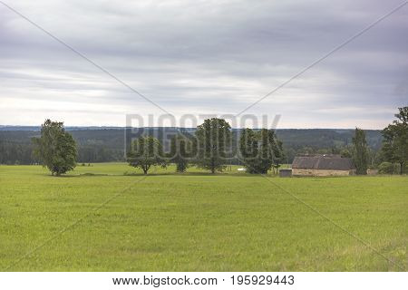 Country side landscape view over meadow with an country house