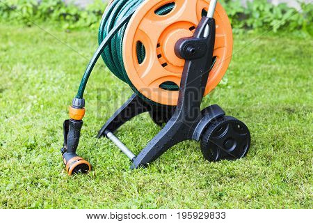 Coiled garden hose on reel grass backgound