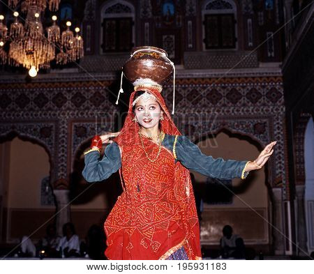 SAMODE, INDIA - NOVEMBER 22, 1993 - Indian dancer balancing a pot on her head performing at the Samode Palace Samode Rajasthan India, November 22, 1993.