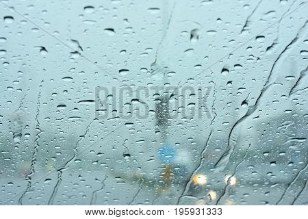 Road view through car window with rain drops.