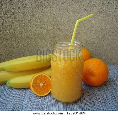 Banana and orange smoothie in a jar, rustic set.