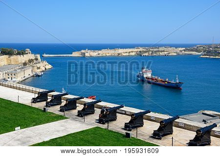 VALLETTA, MALTA - MARCH 30, 2017 - Soldier preparing the cannons ready for the Noon Gun in Upper Barrakka Gardens with views across the Grand Harbour towards Fort Rikasoli Valletta Malta Europe, March 30, 2017.