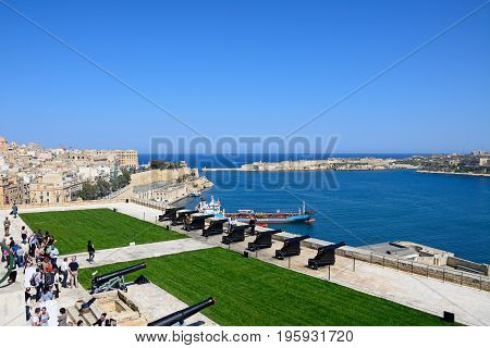 VALLETTA, MALTA - MARCH 30, 2017 - Soldiers preparing the cannons ready for the Noon Gun in Upper Barrakka Gardens with views across the Grand Harbour towards Fort Rikasoli and tourists watching on Valletta Malta Europe, March 30, 2017.