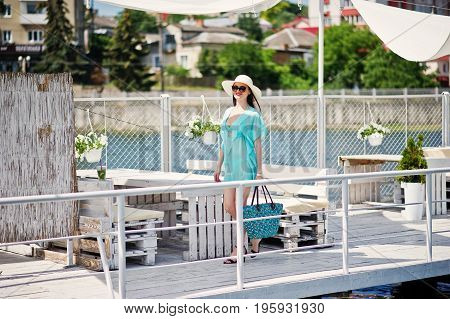 Lovely Girl Wearing Transparent Dress, Hat And Sunglasses Walking On The Quay By The Lake With Her B