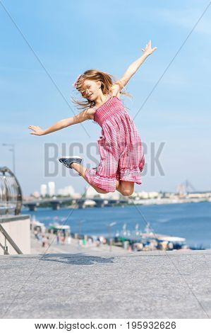 Active kid girl gymnast jumping or dancing on the street. Young girl acrobat. The girl is engaged in gymnastics
