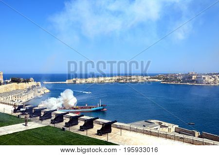 VALLETTA, MALTA - MARCH 30, 2017 - Soldiers firing the cannons for the Noon Gun in Upper Barrakka Gardens with views across the Grand Harbour towards Fort Rikasoli Valletta Malta Europe, March 30, 2017.