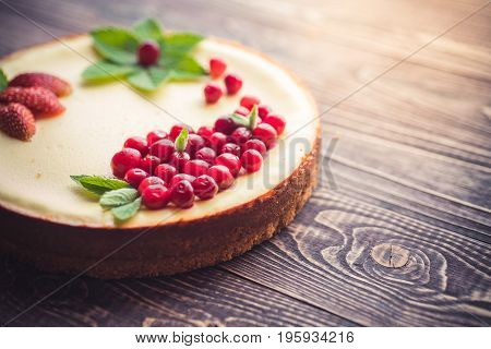 Fresh cheesecake with berries on a wooden background. Copy space