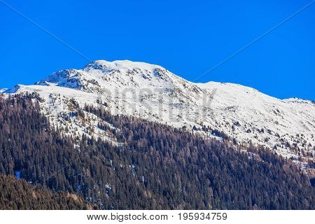 Summits of the Alps in Switzerland in wintertime, view from the town of Davos in the Swiss canton of Graubunden at the end of January.