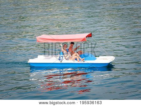 Odessa, Ukraine - July 15, 2016: Two young people on old water bike having fun ride. Young woman and man have fun using water-bicycle at the sea.  Couple on water bicycle