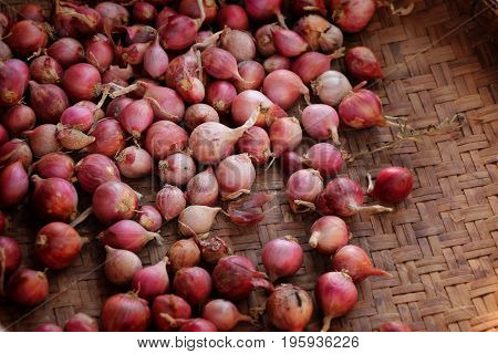 organic small red onion on bamboo basket at local farmer's market in Thailand.