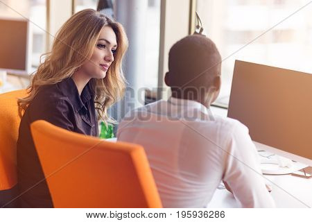 Two creative millenial small business owners working on social media strategy using a computer.