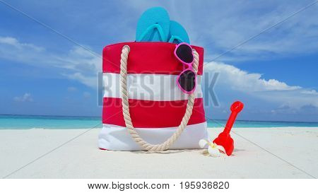 Maldives white sandy beach bag sunglasses flip flops on sunny tropical paradise island with aqua blue sky sea ocean 4k