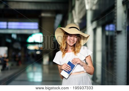 Pretty girl in a wide-brimmed hat with the passport and tickets in a hand. Girl posing. Railway station. Summer holiday.