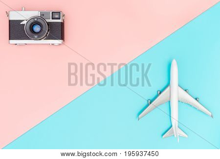 Toy plane and camera on pink and blue background for chic travel concept