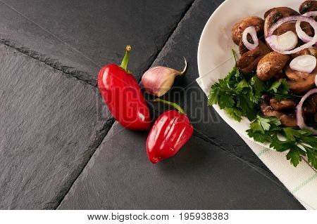 Cooked appetizing tasty fried mushrooms on white plate. Spring harvest of mushrooms cooked for a festive table. Healthy vegetarian food on a dark stone background.